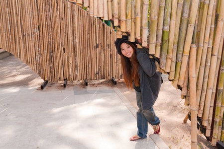 young woman is bending under bamboo arch and smile with relax feeling photo
