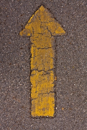 Yellow straight sign on asphalt way texture photo