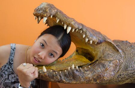 Young woman in danger with crocodile mouth photo