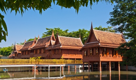 Thai style teak houses in the pond photo