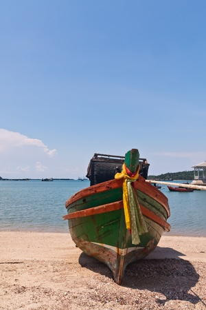 Wooden boat on the beach with beautiful blue sky in background in Thailand from front vertical photo