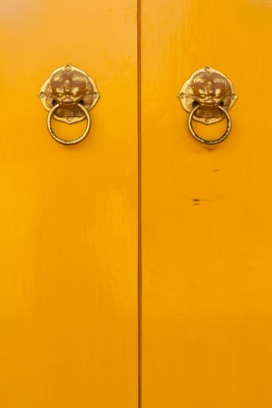 Golden chinese door handles on yellow doors in vertical