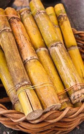 Green sweet sugarcane in wooden basket on floor
