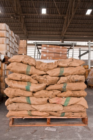 Brown sacks stack on wooden pallet in stockpile