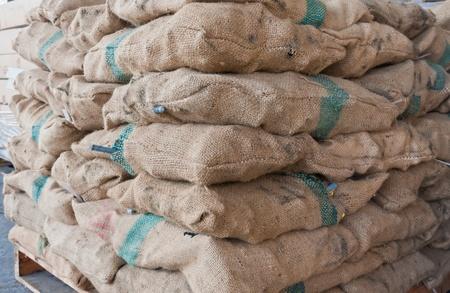 tilted: Brown sacks stack on wooden pallet in stockpile tilted