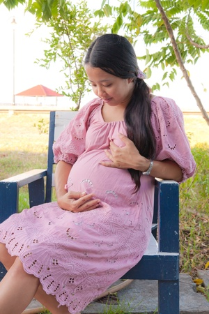 Asian pregnant women in pink dress take care of her pregnancy and smile