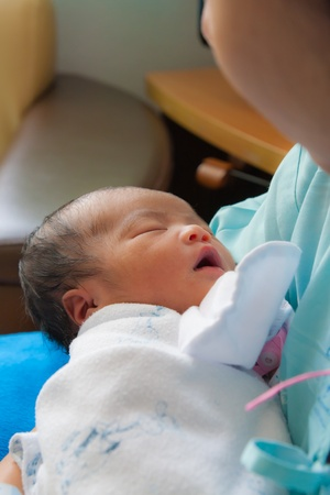 Face of Asian female newborn fall asleep in mother photo