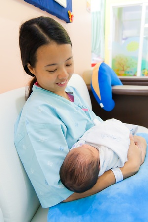 Asian female with sleeping newborn in her arms