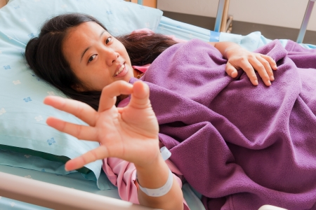 asian hospital: Female patient sowing her two fingers for cheerful