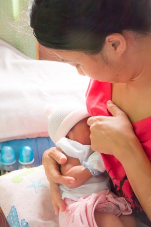 Asian woman breastfeeding her newborn daughter in her arm Stock Photo - 11802469