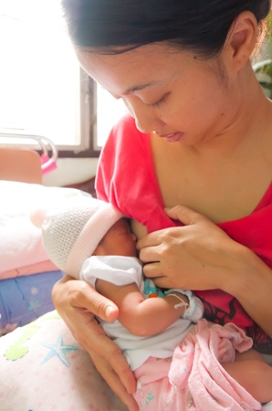 Asian woman breastfeeding her newborn daughter in her arm photo