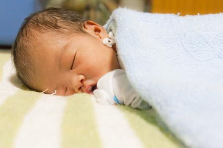 Asian female newborn sleeping on soft bed