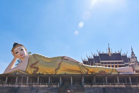 Reclining Buddha statue with blue sky and sun ray photo