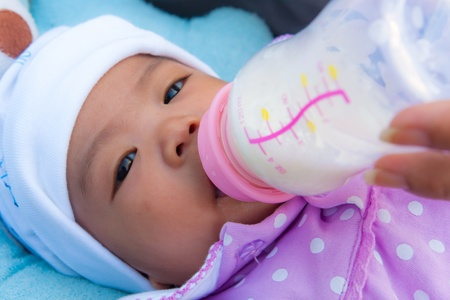 Thai female baby eating milk from plastic bottle photo