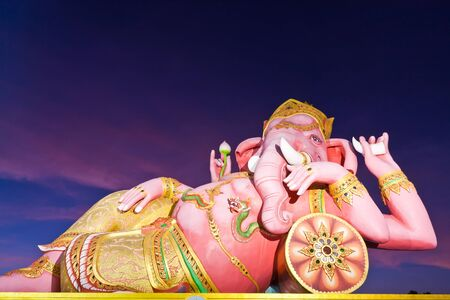 Indian god Ganesha statue in twilight in Thailand photo