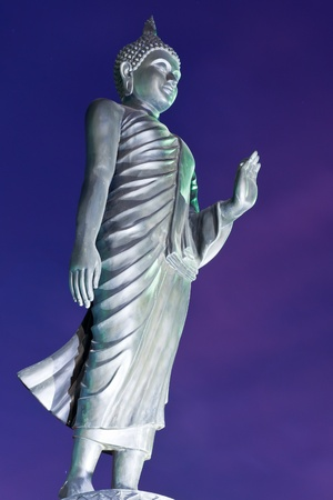 Back of walking Buddha statue with blue sky in twilight tilted photo