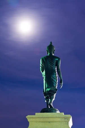 venerate: Back of walking Buddha statue with blue sky in twilight