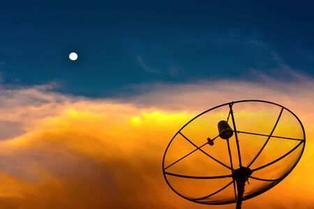 Parabolic satellite dish in twilight time with blue sky and moon photo