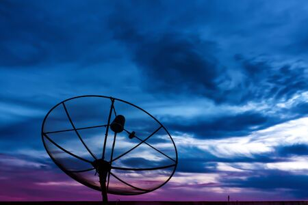 Parabolic satellite dish in twilight time with blue sky photo