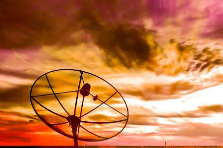 Parabolic satellite dish in twilight time with sun beam photo