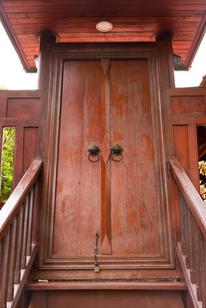 Thai style wooden stairway to wooden door photo