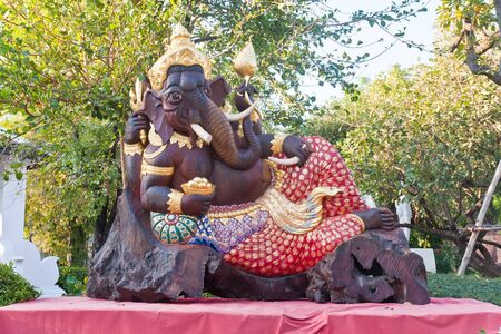 Brown carved wooden Ganesh statue on red table photo
