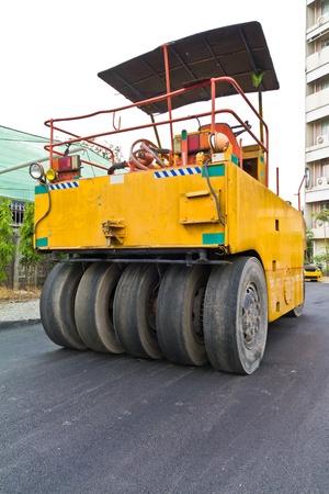 vibroroller: Steamroller on asphalt road under construction from back