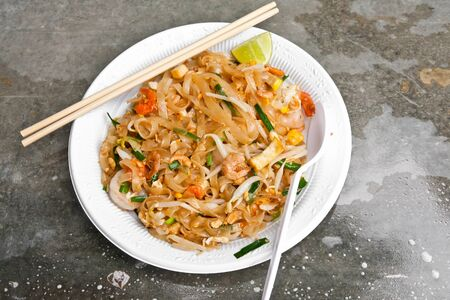 Padthai noodle on plastic dish with chopsticks and spoon photo
