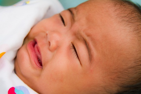 Crying Asian baby face close up on bed