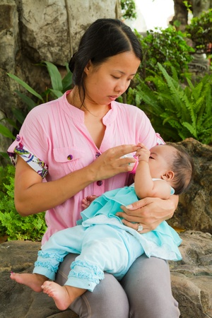 Asian woman feeding her baby with bottle on rock in park photo