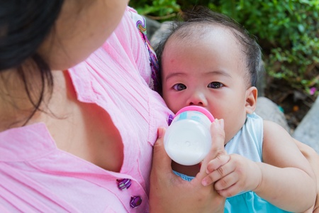 Asian woman feeding her baby with bottle from top Imagens