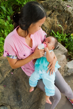 Asian woman feeding her baby with bottle  in park from top vertical photo