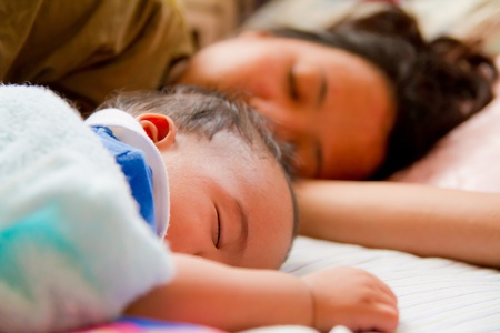 Asian female baby sleeping with her mother on bed Stock Photo - 12354303
