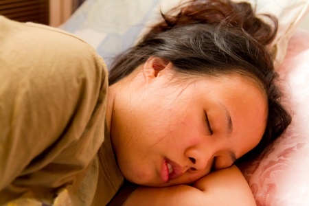 Asian woman closed her eyes and sleeping on bed