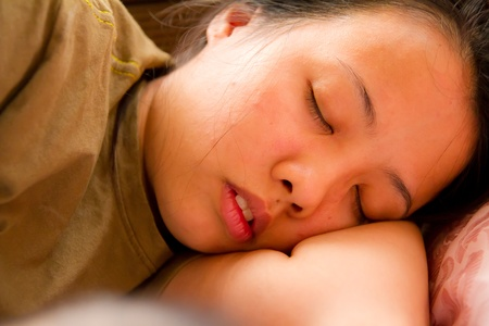 Asian woman closed her eyes and sleeping on bed photo