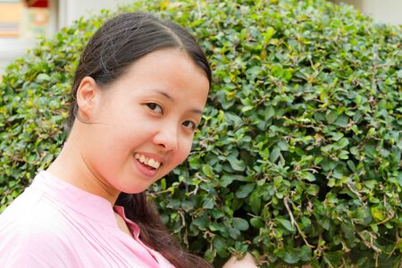 Asian woman smiling in front of tree in park Stock Photo - 12355489