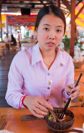 Asian woman eating noodle in the restaurant photo