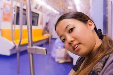 Asian woman sitting and smiling on train photo