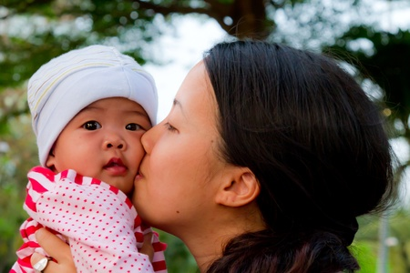 Asian woman kiss her baby daughter in park photo