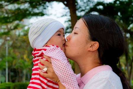 Asian woman kiss her baby daughter in park Stock Photo
