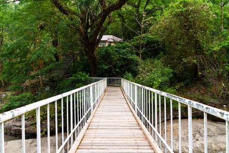 hand rail: Wooden bridge with metal hand rail cross river in forest Stock Photo