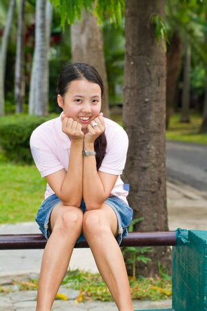 Young asian woman sitting and smile on bench in park photo