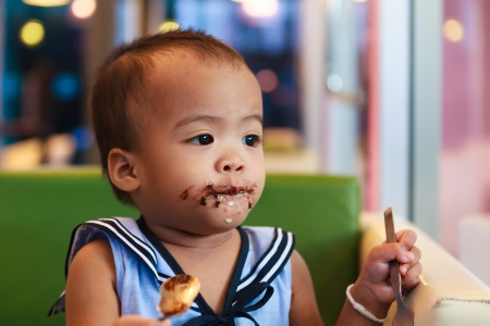 Asian baby girl eating chocolate and mouth is dirty Stock Photo