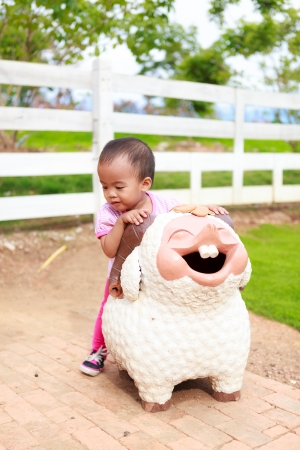 Asian baby girl ride sheep statue in farm photo