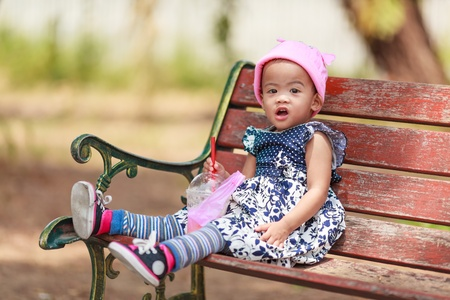 Asian baby girl sitting with beverage on wooden bench alone photo