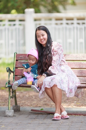 Mother and daughter sitting on wooden bench in park photo