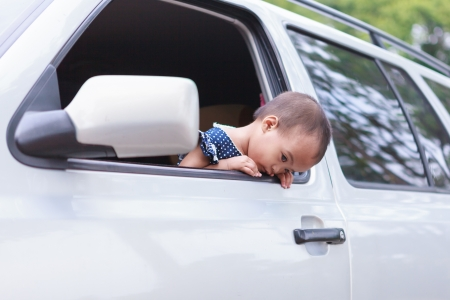 Asian baby girl held out car window with bad feeling face photo