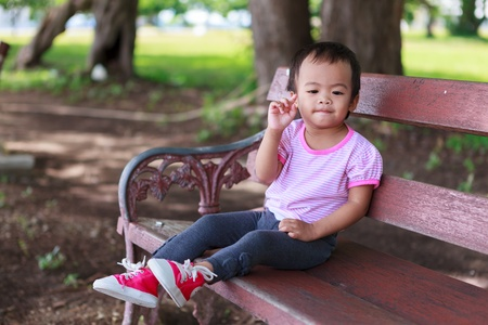 Asian baby girl sitting on wooden bench in park photo