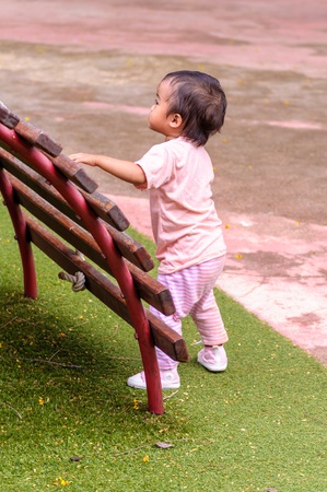 Asian baby girl playing in playground alone photo