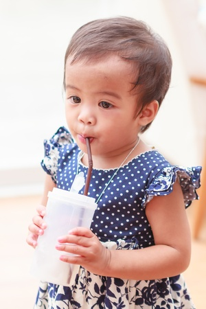 Thai baby girl drinking water by sucking from straw photo